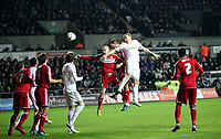 League Cup, Swansea City (white) V Middlesbrough, Liberty Stadium, 12/12/12<br /> Pictured: Garry Monk of Swansea (in white) challenged by Nicky Bailey, heads the ball to score with a Middlesbrough deflection a late goal in the second half to win the game one nil.<br /> Picture by: Ben Wyeth<br /> Athena Picture Agency<br /> info@athena-pictures.com