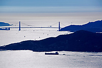 aerial photograph of a silihouette of Angel Island, the Golden Gate bridge and the Marin Headlands with an escorted oil tanker in the foreground
