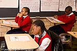 K-8 Parochial School Bronx New York Grade 4 children seated in rows reading from handout in class horizontal
