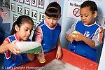 Education Preschool 4-5 year olds water table two girls and a boy playing in sudsy water horizontal