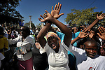 A woman waves her arms in the air as she prays during a Catholic mass in Port-au-Prince marking the one-year anniversary of the January 12, 2010, earthquake that devastated Haiti. Behind her a woman carries photos of loved ones who died during the quake. Held in the shadows of the ruins of the city's Catholic cathedral, the gathering was one of many special observances held throughout the Caribbean nation...