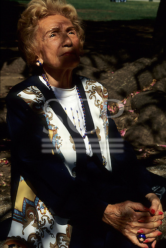 Richmond Park, England. Well-dressed elderly woman sitting in the park with her hands clasped. Suzanna Mares.