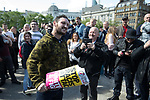 """© Joel Goodman - 07973 332324 . 11/06/2017 . Manchester , UK . A demonstrator eats a piece of an anti-fascists placard that was grabbed from anti-fascist protesters . Demonstration against Islamic hate , organised by former EDL leader Tommy Robinson's """" UK Against Hate """" and opposed by a counter demonstration of anti-fascist groups . UK Against Hate say their silent march from Piccadilly Train Station to a rally in Piccadilly Gardens in central Manchester is in response to a terrorist attack at an Ariana Grande concert in Manchester , and is on the anniversary of the gun massacre at the Pulse nightclub in Orlando . Photo credit : Joel Goodman"""