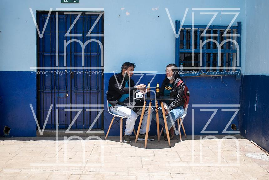 """BOGOTA - COLOMBIA, 05-09-2020: Comensales disfrutan de una cerveza durante el primer día del piloto de apertura de restaurantes y cafés al aire libre, denominado """"Bogotá a Cielo Abierto"""", en el Chorro de Quevedo en el centro de Bogotá que ahora tiene sus calles pintadas con formas geométricas en pintura neón y cuenta con mesas, distribuidas estratégicamente para mantener el distanciamiento físico al finalizar la cuarentena total en el territorio colombiano causada por la pandemia  del Coronavirus, COVID-19. / Customers enjoy a beer during the first day of the pilot for the opening of restaurants and outdoor cafes, called """"Bogotá a Cielo Abierto"""", in Chorro de Quevedo in the center of Bogotá, which now has its streets painted with geometric shapes in neon paint and has tables, strategically distributed to maintain physical distancing at the end of the total quarantine in the Colombian territory caused by the Coronavirus pandemic, COVID-19. Photo: VizzorImage / Johan Rugeles / Cont"""
