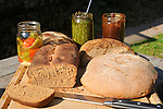 Various whole grain breads and canned peppers, pesto, and apple butter.