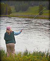 Female in pink hat fly fishing at edge of river