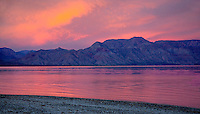 THE SUNRISE CASTS A RED GLOW OVER THE SEA OF CORTEZ AND SURROUNDING MOUNTAINS IN BAJA CALIFORNIA, MEXICO