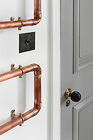 Copper pipes mounted onto the pantry walls with brass brackets make an appealing feature against the bright white background