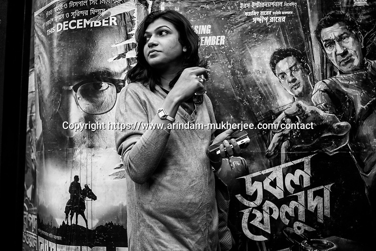 Dipmalya(Diya) drinks tea in front of a bengali movie poster, Kolkata, India. Arindam Mukherjee