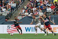 FOXBOROUGH, MA - JULY 25: Djordje Mihailovic #8 of CF Montreal dribbles as Arnor Traustason #25 of New England Revolution defends during a game between CF Montreal and New England Revolution at Gillette Stadium on July 25, 2021 in Foxborough, Massachusetts.