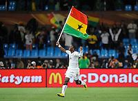 John Pantsil of Ghana celebrates victory with the flag of Ghana