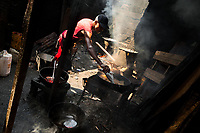 An Afro-Colombian cook throws a fish into boiling oil in a street restaurant in the market of Bazurto in Cartagena, Colombia, 16 December 2017. Far from the touristy places in the walled city, a colorful, vibrant labyrinth of Cartagena's biggest open-air market sprawls to the Caribbean seashore. Here, in the dark and narrow alleys, full of scrappy stalls selling fruit, vegetables and herbs, meat and raw fish, with smelly garbage on the floor and loud reggaeton music in the air, the African roots of Colombia are manifested.