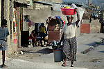 A basin on her head, a woman walks along the street in Cite Soleil, a sprawling poor portion of Port-au-Prince, Haiti.