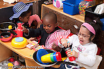 Education Preschool 3-5 year olds group of two girls and a boy in dressup clothes in kitchen area playing and talking