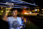 Fishing Cat (Prionailurus viverrinus) biologist, Anya Ratnayaka, tracking cat next to canal in city at night, Urban Fishing Cat Project, Colombo, Sri Lanka