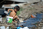 """THIS PHOTO IS AVAILABLE AS A PRINT OR FOR PERSONAL USE. CLICK ON """"ADD TO CART"""" TO SEE PRICING OPTIONS.   A Roma girl collects drinking water from a dirty stream flowing through the Maxsuda neighborhood of Varna, Bulgaria."""