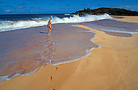 A solitary woman in a bathing suit walks along pristine Papohaku Beach on Molokai.