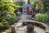 Bocce ball court between tool shed and stone patio with fireplace in Habets backyard garden, Pleasant Hill, California