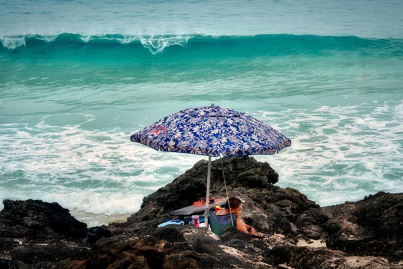 Man under umbrella and ocean waves. Kua Bay, Hawaii, the big island.