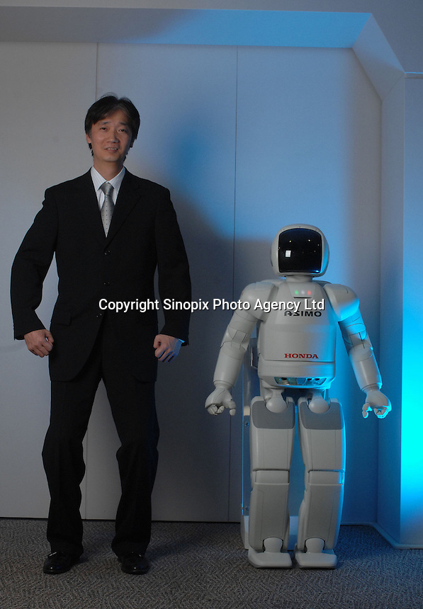 """The Asimo robot built by Honda with it's developer and chief engineer Masato Hirose at the Honda headquarters in Tokyo where it lives in the office and performs simple tasks. Asimo is one of the most advanced humanoids in the world and is being developed as a """"home"""" help robot."""
