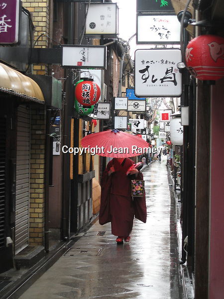 A Geisha walks through Pontocho with a red umbrella - Kyoto