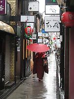 A Geisha walks through Pontocho with a red umbrella - Kyoto