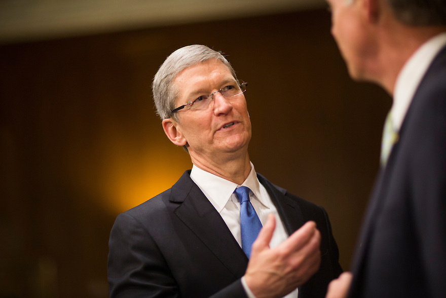 Apple CEO Tim Cook speaks with a senator during a break in his testimony at a Senate homeland security and governmental affairs investigations subcommittee hearing on offshore profit shifting and the U.S. tax code, on Capitol Hill in Washington. Apple Inc's chief executive officer defended the company's tax record during a Senate hearing where lawmakers said the maker of iPads, iPods and Mac computers kept billions of dollars in profits in Irish subsidiaries to avoid U.S. taxes.  He was joined by Apple's Head of Tax Operations Philip Bullock ®  and CFO Peter Oppenheimer (L).