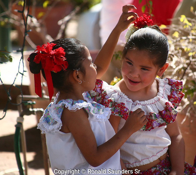 Girl adjusts her friend's ribbon in her hair prior to the festival