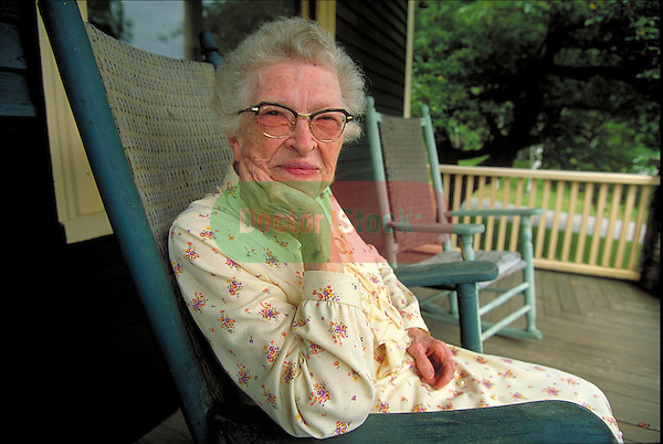 portrait of elder woman sitting on porch in rocking chair