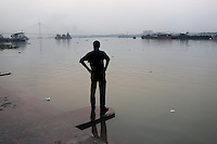 A man stands on the banks of the Ganges River, in central Kolkata. India. November, 2013