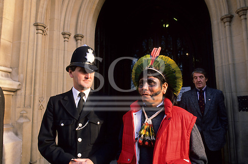 London, England. Paulinho Payakan (Bep Koroti Kayapo), international figurehead for the Kayapo, with a British policeman outside the Houses of Parliament in Westminster wearing his feather cocaa and black war paint; 1989.