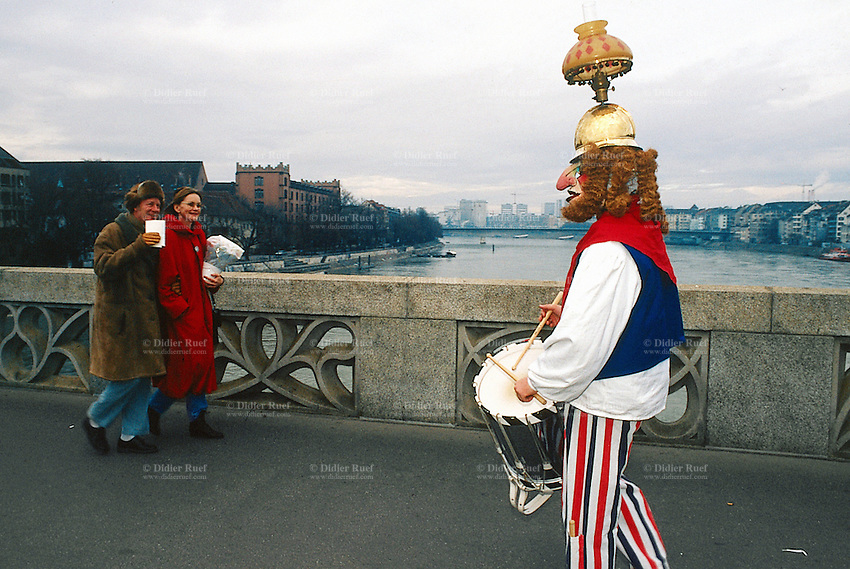 """Switzerland. Basel.  River Rhine. Fasnacht Carnival. A musician from a """"Clique"""" walks on the bridge and plays the drum with a light table fixed on a golden helmet. A  """"Clique""""  is a group of persons playing music in the streets during the three days of the Fasnacht Carnival.© 1997 Didier Ruef"""