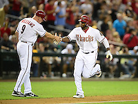 Apr. 23, 2012; Phoenix, AZ, USA; Arizona Diamondbacks outfielder Justin Upton (right) is congratulated by third base coach Matt Williams after hitting a solo home run against the Philadelphia Phillies in the fourth inning at Chase Field. Mandatory Credit: Mark J. Rebilas-