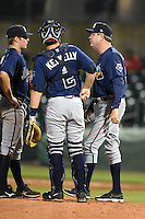 Mississippi Braves pitching coach Dennis Lewallyn (50) talks with pitcher Jason Hursh (8) as catcher Matt Kennelly (2) listens in during a game against the Montgomery Biscuits on April 21, 2014 at Riverwalk Stadium in Montgomery, Alabama.  Montgomery defeated Mississippi 6-2.  (Mike Janes/Four Seam Images)