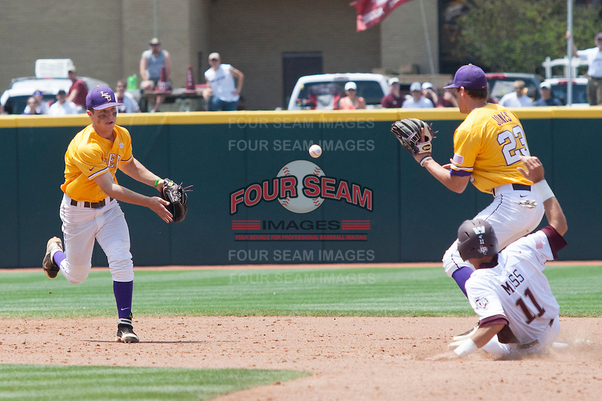LSU Tigers shortstop Alex Bregman (30) toss the ball to second baseman JaCoby Jones (23) before Texas A&M Aggies base runner JB Moss (11) slides into second for the last out of the the NCAA Southeastern Conference baseball game on May 11, 2013 at Blue Bell Park in College Station, Texas. LSU defeated Texas A&M 2-1 in extra innings to capture the SEC West Championship. (Andrew Woolley/Four Seam Images).