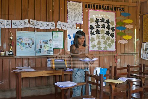 Pará State, Brazil. Aldeia Pukararankre (Kayapo). Teacher Ireroko Kayapo in the school preparing for a test.