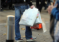 Pictured: A young male shopper with many bags in Oxford Street, Swansea, south Wales. Friday 28 November 2014<br />