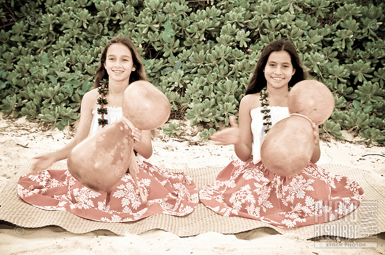 Two girls with ipuheke (gourds) doing a noho (seated) hula wearing kukui nut leis