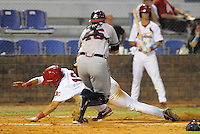 Infielder Neil Pritchard (12) of the Johnson City Cardinals slides home safely as catcher Chad Comer (46) of the Danville Braves tries a sweep tag in a game on August 19, 2011, at Howard Johnson Field in Johnson City, Tennessee. Danville defeated Johnson City, 5-4, in 16 innings. (Tom Priddy/Four Seam Images)