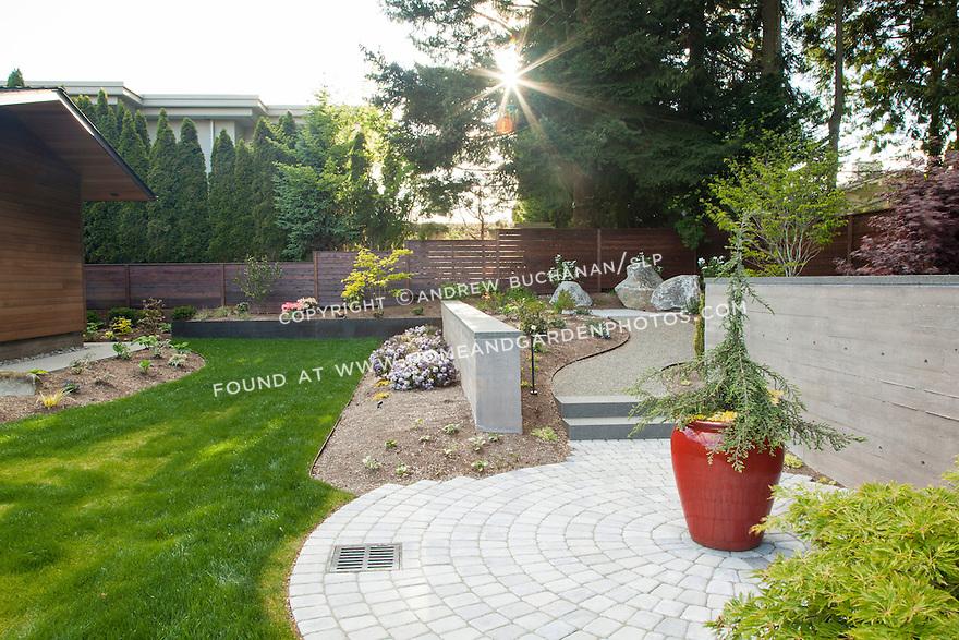 Backyard with circular stone patio, lawn, and garden beds