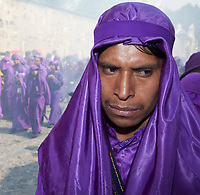 Antigua, Guatemala.   A Cucurucho Accompanying a Religious Procession during Holy Week, La Semana Santa.  Clouds of Incense in Background.