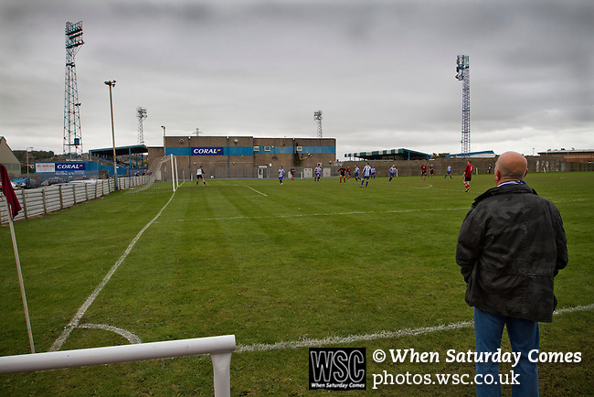 Barrow AFC 0 Newport County 3, 15/09/2012. Furness Building Society Stadium, Football Conference. A spectator watching West Lancashire Football League Furness Rovers playing on their Strawberry fields pitch adjacent to Barrow AFC's Furness Building Society Stadium during the delayed kick-off of the Barrow v Newport County Conference National Fixture. Newport County eventually won the match by 3-0, watched by 802 spectators. Both Barrow and Newport County from Wales were former members of the Football League in England. Photo by Colin McPherson.