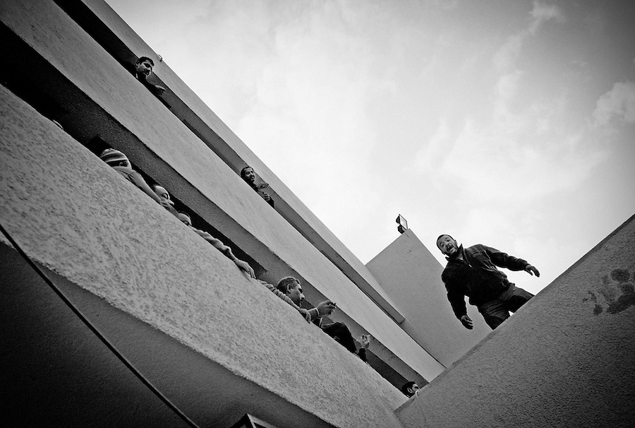 An Egyptian voter gestures on the roof while others wait in line at the polling station in Tawfikia Secondary School, Shubra, Cairo, Egypt, Monday, Nov. 28, 2011. Voting began on Monday in Egypt's first parliamentary elections since longtime authoritarian leader Hosni Mubarak was ousted in a popular uprising nine months ago. The vote is a milestone many Egyptians hope will usher in a democratic age after decades of dictatorship.