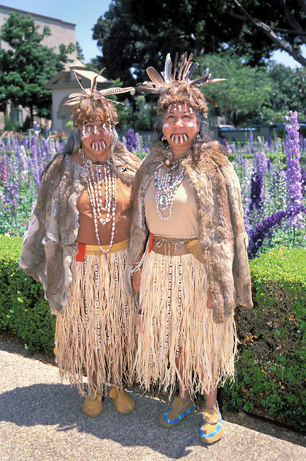 Two sisters dressed traditionally of the Mission people, more specific the Costanoan Rumsen Ohlone tribe, are dressed in traditional rabbit skin capes, grass skirts, shell beads and feather headdresses at the Museum of Man in Balboa Park San Diego CA