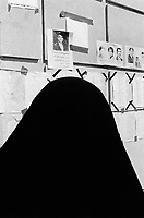 """Iraq. Baghdad. A woman dressed with a black veil covering her head reads the dead people list taped on the wall. The """" Committee for free prisoners"""" establishes various lists of the people which were executed by Saddam Hussein regime. Families come everyday to read the lists and collect informations on their loved parents, hoping to know their whereabouts. © 2003 Didier Ruef"""