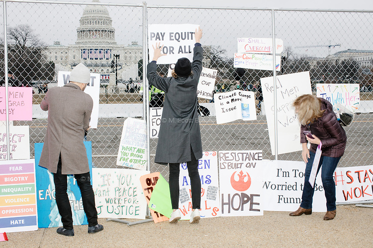 People hung protest signs on a fence near the US Capitol building after the Women's March on Washington protest and demonstration in opposition to newly inaugurated President Donald Trump on Jan. 21, 2017.