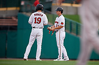 Rochester Red Wings Brent Rooker (19) hands his gear to Brian Schales (13) during an International League game against the Pawtucket Red Sox on June 28, 2019 at Frontier Field in Rochester, New York.  Pawtucket defeated Rochester 8-5.  (Mike Janes/Four Seam Images)