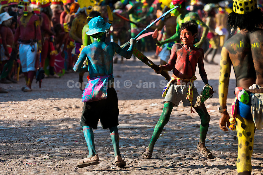 """Cora Indian boys fight wooden sword duel during the religious ritual ceremony of Semana Santa (Holy Week) in Jesús María, Nayarit, Mexico, 23 April 2011. The annual week-long Easter festivity (called """"La Judea""""), performed in the rugged mountain country of Sierra del Nayar, merges indigenous tradition (agricultural cycle and the regeneration of life worshipping) and animistic beliefs with the Christian dogma. Each year in the spring, the Cora villages are taken over by hundreds of wildly running men. Painted all over their semi-naked bodies, fighting ritual battles with wooden swords and dancing crazily, they perform demons (the evil) that metaphorically chase Jesus Christ, kill him, but finally fail due to his resurrection. La Judea, the Holy Week sacred spectacle, represents the most truthful expression of the Coras' culture, religiosity and identity."""