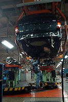 "A worker assembles parts of a ""Grand Cherokee"" of Chrysler in the Beijing Jeep factory.."