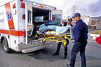 EMTs place car accident victim into ambulance